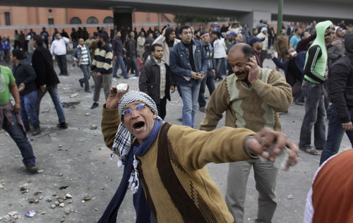 An anti-government protester throws rocks at pro-government supporters, while another talks on his mobile phone, right, during clashes between the two sides near the Egyptian Museum in downtown Cairo, Egypt, Thursday, Feb. 3, 2011. Protesters and regime supporters skirmished in a second day of rock-throwing battles at a central Cairo square while new lawlessness spread around the city. (AP Photo/Ben Curtis)