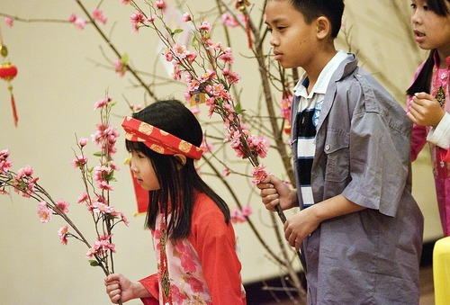 Djamila Grossman  |  The Salt Lake Tribune The Vietnamese Community in Utah is celebrating the Lunar New Year with a big festival. From left, Lan Anh Vu, 7, Dean Pham, 10, and Rose Nguyen, 8, hold budding branches as they practice a dance at Lien Hoa Buddhist Temple in Taylorsville.