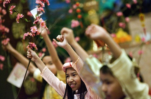 Djamila Grossman  |  The Salt Lake Tribune Emily Nguyen, 10, and other children hold up branches as they practice a dance they will be performing during the Tet celebration.