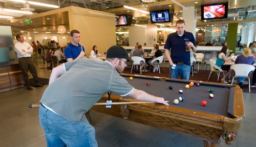 Al Hartmann  |  The Salt Lake Tribune file photo  Jeff McDonald shoots a game of pool with fellow employeesduring lunch break. Provo-based APX Alarm Security Solutions Inc. has changed its name and expanded its business to begin offering home automation equipment and services.