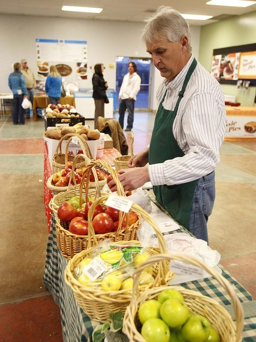 TRENT NELSON | The Salt Lake Tribune Kirk Rogers of Fowers Fruit Ranch stocks produce at an indoor Farmers Market in Salt Lake City. Rep. Bill Wright, R-Holden, has a bill to exempt Utah-produced and sold food from federal regulation.