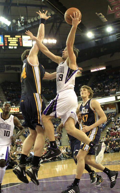 Sacramento Kings guard Beno Udrih, of Slovenia, center, goes to the basket against Utah Jazz center Kyrylo Fesenko, of the Ukraine, left, during the third quarter of an NBA basketball game in Sacramento, Calif., Monday, Feb. 7, 2011. The Jazz won 107-104. (AP Photo/Rich Pedroncelli)