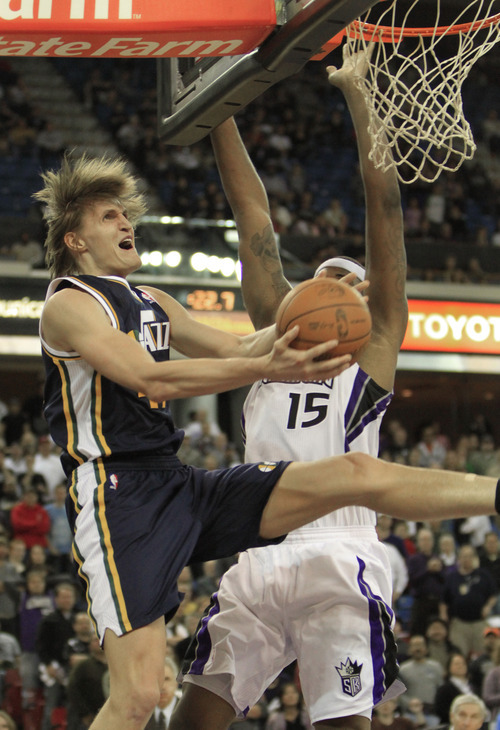 Utah Jazz forward Andrei Kirilenko, of Russia, left, is fouled as he goes to the basket by Sacramento Kings center DeMarcus Cousins during the fourth quarter of an NBA basketball game in Sacramento, Calif., Monday, Feb. 7, 2011. The Jazz won 107-104. (AP Photo/Rich Pedroncelli)