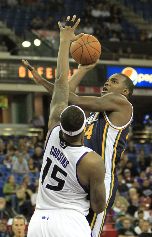 Utah Jazz forward Paul Millsap, right, shoots over Sacramento Kings center DeMarcus Cousins during the fourth quarter of an NBA basketball game in Sacramento, Calif., Monday, Feb. 7, 2011. The Jazz won 107-104. (AP Photo/Rich Pedroncelli)