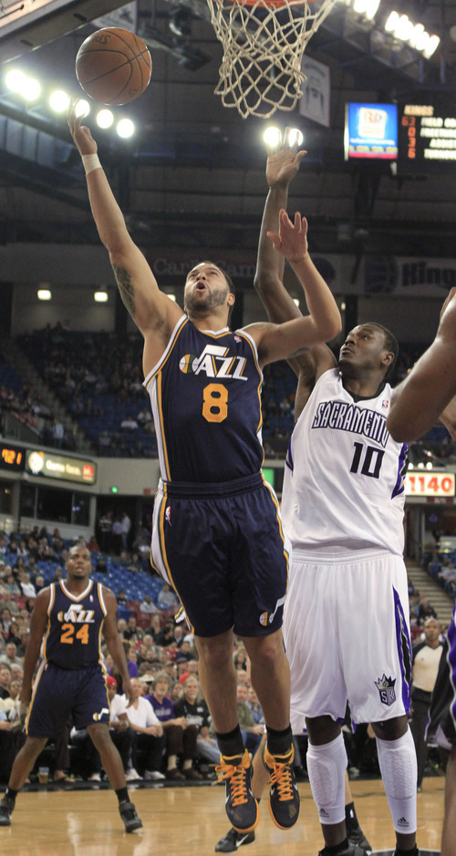Utah Jazz guard Deron Wiliams, left, lays up the ball past Sacramento Kings center Samuel Dalembert during the first quarter of an NBA basketball game in Sacramento, Calif., Monday, Feb. 7, 2011. (AP Photo/Rich Pedroncelli)