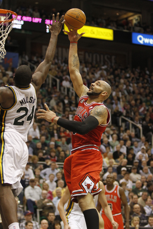 Rick Egan  |  The Salt Lake Tribune  Carlos Boozer shoots over Paul Milsap,  in NBA action Utah vs. Chicago, in Salt Lake City, Wednesday, February 9, 2011