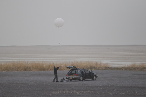 University of Utah graduate student Erik Crosman launches a weather balloon from the shore of the Great Salt Lake as part of a study on the Salt Lake Valley's inversions.  Photo by Bryan Jones