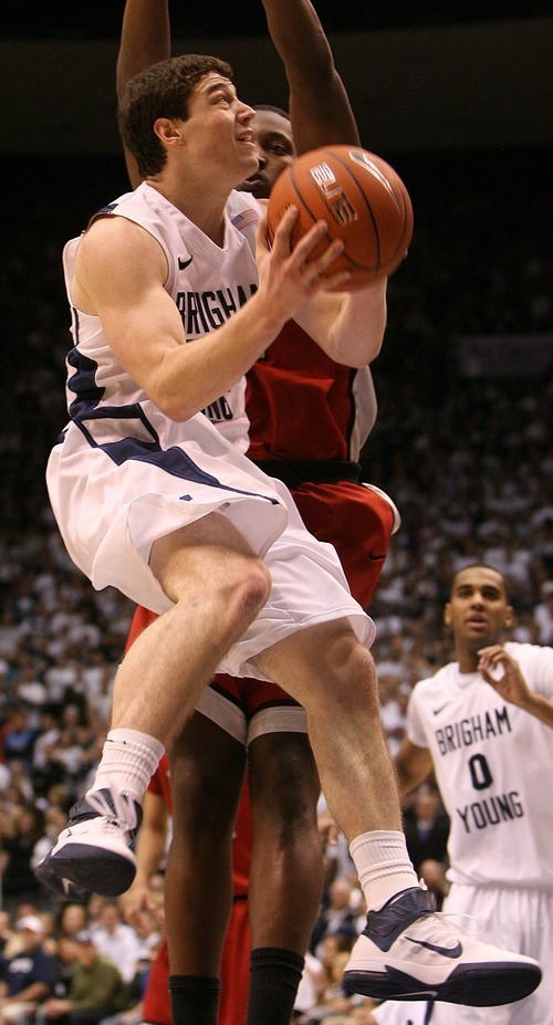 Leah Hogsten  |  The Salt Lake Tribune BYU guard Jimmer Fredette (32) runs in for a lay up over UNLV forward Quintrell Thomas (1).  The Brigham Young University Cougars defeated UNLV Saturday, February 5, 2011, in Provo, 78-64 at the Marriott Center.
