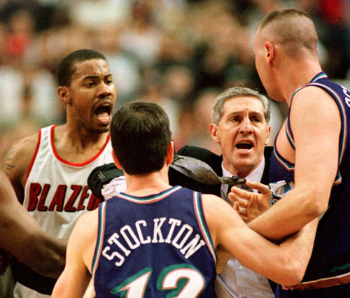 Utah Jazz coach Jerry Sloan, second from right, and John Stockton jump in to keep Utah's Greg Ostertag, right, from Portland Trail Blazers Rasheed Wallace, left, after Ostertag got into a fight with  Trail Blazers' Steve Smith during the fourth quarter of their NBA game in Portland, Ore., Sunday, Feb., 27, 2000. (AP Photo/Greg Wahl-Stephens)