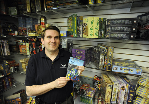 Sarah A. Miller  |  The Salt Lake Tribune Standing next to a wall full of board games at his retail store in Layton, Mayday Games owner Seth Hiatt holds a bag of tokens -- the kind of accessories also sold by his company to gaming enthusiasts.