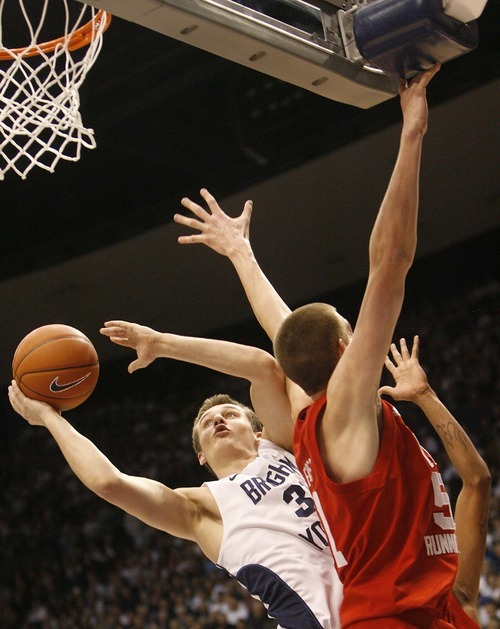 Trent Nelson  |  The Salt Lake Tribune BYU's Kyle Collinsworth shoots around Utah's David Foster in the first half at BYU vs. Utah, college basketball in Provo, Utah, Saturday, February 12, 2011.