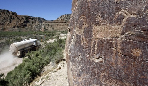 Al Hartmann  |  Tribune file photo Service vehicles from the nearby gas wells kick up dust in Nine Mile Canyon. The dust is believed to damage the rock art panels. Critics of a proposal to pave the old road say it wouldn't permanently protect the antiquities.