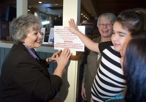 Paul Fraughton  |  The Salt Lake Tribune    Rep. Ronda Menlove, left, with the help of Briar Daniel, 5, who has effects from  Fetal Alcohol Syndrome, put up a sign at  a local  Chili's warning of the effects of alcohol to pregnant women. Standing in the rear is Dr. Susan Lewin.  on   Friday,February 18, 2011
