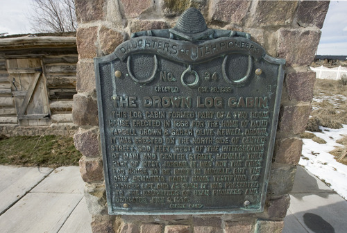 Steve Griffin  |  The Salt Lake Tribune    A Daughters of the Utah Pioneers plaque marks the site of the the Drown Log Cabin in Midvale on Thursday, Feb. 17, 2011.  The cabin was erected in 1866 and is the last standing pioneer farm home in the Midvale area. Chelsea Rushton is the director of the Midvale Museum and with the help of others is restoring the cabin.