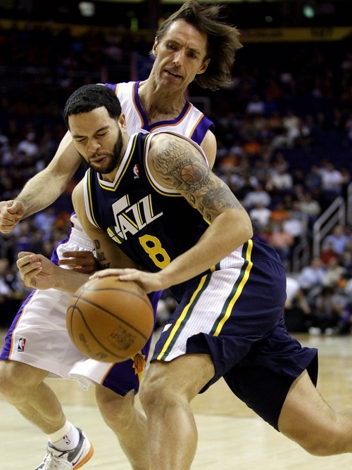 Utah Jazz guard Deron Williams (8) drives against Phoenix Suns guard Steve Nash during the first quarter of an NBA basketball game, Tuesday, Feb. 15, 2011, in Phoenix. Williams is being traded to the New Jersey Nets. (AP Photo/Matt York)