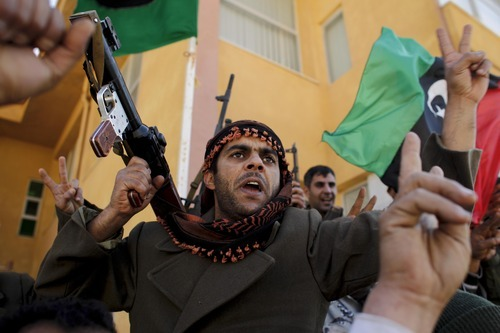 Tara Todras-Whitehill     The Associated Press Libyan soliders who now call themselves the Free Libyan Army shout as the pose for pictures at the main army base in the eastern city of Tobruk Friday.