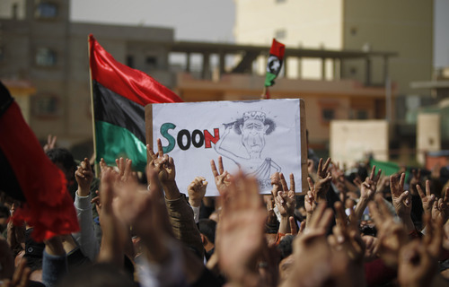 Tara Todras-Whitehill     The Associated Press A poster depicting Libya's leader Moammar Gadhafi is displayed as Libyans protest in Kings Square after Friday prayers in the eastern city of Tobruk Friday.