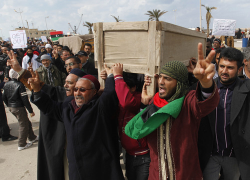 Hussein Malla     The Associated Press Mourners on Friday carry the coffins of two protesters killed last week during the demonstrations against Libyan leader Moammar Ghadafi in Benghazi. Militias loyal to Gadhafi opened fire on protesters streaming out of mosques in the Libyan capital on Friday, demanding the regime's ouster, witnesses said, reporting at least four killed. Across rebellious cities in the east, tens of thousands held rallies in support of the first Tripoli protests in days.