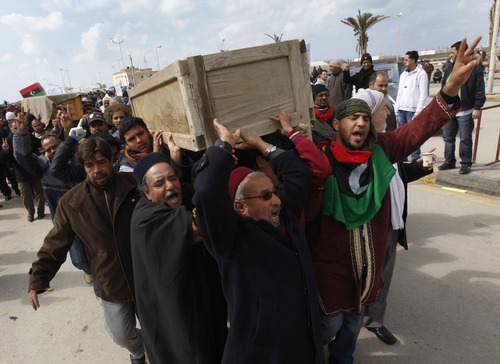 Hussein Malla     The Associated Press Libyan mourners carry the coffins of two protesters who were killed last week during the demonstrations against Libyan Leader Moammar Ghadafi in Benghazi, Libya, on Friday.