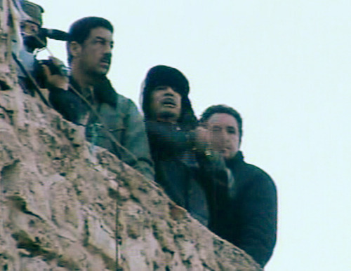 In this  footage taken from Libya State Television, showing Libyan leader Moammar Gadhafi, centre, as he speaks to followers from the top of a stone wall in The Green Square, Tripoli, Libya, Friday, Feb. 25, 2011.  The TV station declared this to be a live broadcast and also showed a large crowd celebrating in the square below.  (AP Photo/Libya State) TV OUT