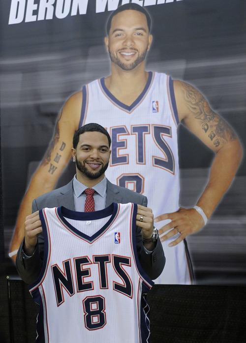 New Jersey Nets Deron Williams poses in front of his poster at a news conference Thursday, Feb. 24, 2011 in East Rutherford, N.J. (AP Photo/Bill Kostroun)