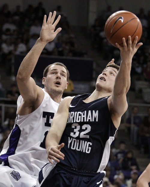 BYU guard Jimmer Fredette (32) attempts a shot as TCU 's Nikola Cerina, left, defends in the second half of an NCAA college basketball game Saturday, Feb. 19, 2011, in Fort Worth, Texas. BYU won 79-56. (AP Photo/Tony Gutierrez)