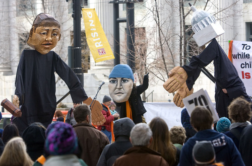 Al Hartmann   |  The Salt Lake Tribune  Puppets of a federal judge, left, Tim DeChristopher, center, and NASA climatologist James Hansenare are used in a skit during a rally to support DeChristopher across the street from the federal couthouse where his trial is set to begin Monday.