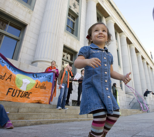 Al Hartmann   |  The Salt Lake Tribune  Coral Floyd, 3, dances to music on the steps of the Frank Moss Federal Court in Salt Lake City on Tuesday, March 1 during the first day of Tim DeChristopher's trial.  Coral was with her Mother Lindsy Floyd who was among a group supporting the eco-activist, who is on trial for disrupting an oil and gas lease auction.