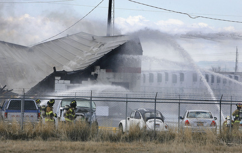 Scott Sommerdorf  |  The Salt Lake Tribune Fire crews douse blaze at building housing The Cartel and Clear Sky Biofuels in Clearfield Friday. The fire also destroyed an adjacent building. The fire was sparked by an explosion at the biofuels business.