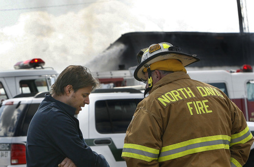 Scott Sommerdorf  |  The Salt Lake Tribune Gary Clark, co-owner and chemical engineer at Clear Sky Biofuels, talks to a North Davis firefighter about his escape from the building after an explosion and fire that sent a fireball past his office door in Clearfield Friday. His business and an automotive repair business were destroyed.