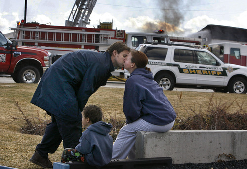 Scott Sommerdorf  |  The Salt Lake Tribune Gary Clark, a co-owner of Clear Sky Biofuels in Clearfield, kisses his wife, Lisa, after narrowly escaping fire that destroyed his business Friday. The Clarks and their 4-year-old son, Corbin, watched the flames from a playground across the street from the business.