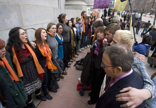 Al Hartmann   |  The Salt Lake Tribune  Tim DeChristopher supporters sing together in a circle of solidarity outside the Frank Moss Federal Courthouse in Salt Lake City March 3 after DeChristopher  was found guilty of crashing a federal oil and gas lease auction .