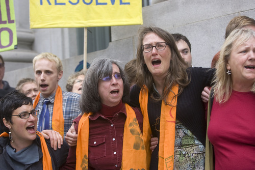 AL HARTMANN   |  Tribune File Photos Tim DeChristopher supporters Joan Gregory, left, and Krista Bowers, right, sing and get emotional outside the Frank Moss Federal Courthouse in Salt Lake City in March after DeChristopher  was found guilty of crashing a federal oil and gas lease auction. Both were arrested in the protest in the Interior Department headquarters in Washington, D.C., on Monday.