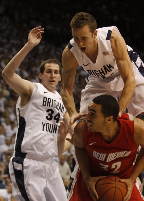 Rick Egan  |  The Salt Lake Tribune  BYU guard Jackson Emery (4) lands on the back of Drew Gordon (32) New Mexico, in Mountain West Basketball action, BYU vs New Mexico in the Marriott Center in Provo, Wednesday, March 2, 201. BYU forward Noah Hartsock (34) is on the left.