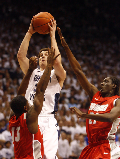 Djamila Grossman | The Salt Lake   BYU guard Jimmer Fredette (32) takes a shot as he is double teamed by Jamal Fenton (13) and Tony Snell (21) New Mexico State, in Mountain West Basketball action at the Marriott Center in Provo, Wednesday, March 2, 2011