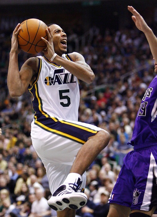 Djamila Grossman  |  The Salt Lake Tribune  The Utah Jazz' Devin Harris (5) jumps up to score as the Sacramento Kings' Beno Udrih (19) tries to block the shot during a game at Energy Solutions Arena in Salt Lake City, Utah, on Saturday, March 5, 2011. The Jazz won the game.