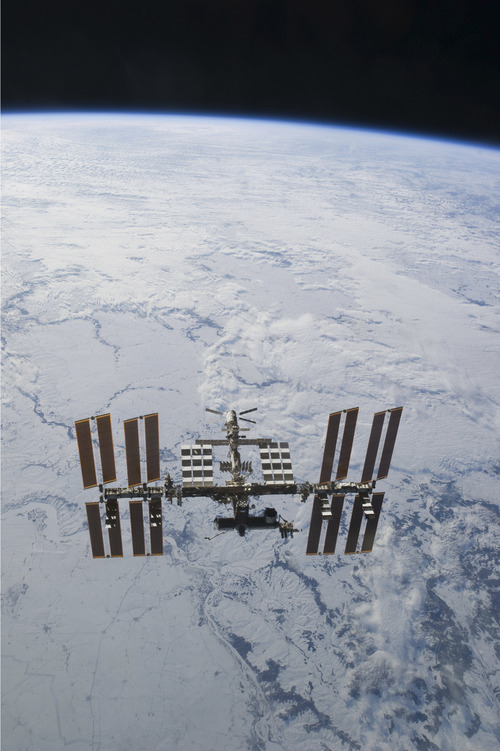 In this image provided by NASA the International Space Station is seen from Discovery backdropped against clouds over Earth, as the two orbital spacecraft accomplish their relative separation on March 7, 2011 after an aggregate of 12 astronauts and cosmonauts worked together for over a week. During a post undocking fly-around, the crew members aboard the two spacecraft collected a series of photos of each other's vehicle. Discovery is on the verge of ending its nearly 27-year flying career. Landing is set for Wednesday. (AP Photo/NASA)
