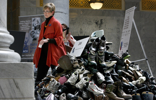 Scott Sommerdorf  |  The Salt Lake Tribune Rep. Becky Edwards, R-North Salt Lake, walks past a stack of 980 shoes after having spoken at the podium at an Autism Council of Utah event in the Capitol rotunda, Thursday, March 10, 2011. Each of these individual shoes represents 10 children with autism in the state. The figure is based on a 2006 estimate that totaled 9,800 kids with autism in the state. Rep. Edwards was instrumental in getting the Autism Council a specialized Utah license plate this year.