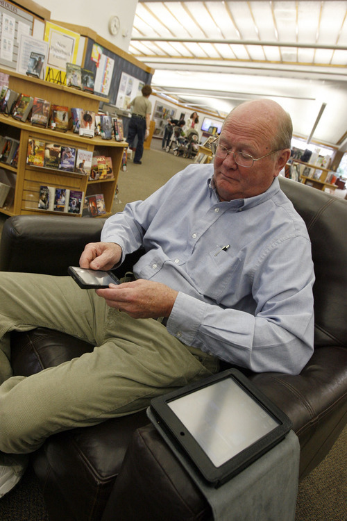 Francisco Kjolseth     The Salt Lake Tribune Jim Behling of Murray reads a book on his Droid X while visiting the Whitmore Library on Wednesday, March 9, 2011. The Salt Lake County Library system has offered the OverDrive e-book system to patrons for more than a year. Now the Salt Lake City Library has adopted the same system, which it rolled out Feb. 17.