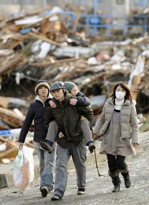 A family walks past flattened houses in Sendai, Miyagi Prefecture, Saturday morning, March 12, 2011 after Japan's biggest recorded earthquake slammed into its eastern coast Friday. (AP Photo/Kyodo News)  MANDATORY CREDIT, NO LICENSING ALLOWED IN CHINA, HONG  KONG, JAPAN, SOUTH KOREA AND FRANCE