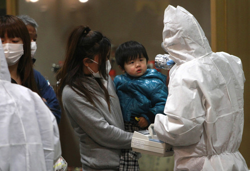 A child is screened for radiation exposure at a testing center Tuesday, March 15, 2011, in Koriyama city, Fukushima Prefecture, Japan, after a nuclear power plant on the coast of the prefecture was damaged by Friday's earthquake. (AP Photo/Wally Santana)