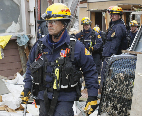 U.S. search and rescue team members search through the rubble in Ofunato, Iwate Prefecture, northern Japan, Tuesday March 15, 2011, after Friday's earthquake and tsunami. (AP Photo/Kyodo News)