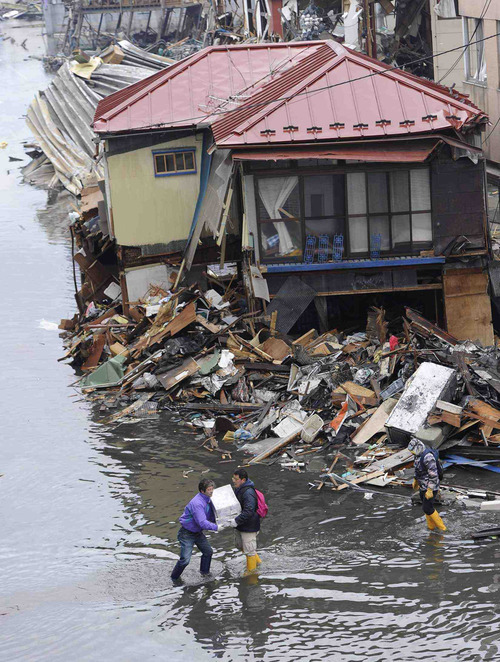 People carry their furniture from their ruined home Tuesday, March 15, 2011, in Kesennuma, Miyagi Prefecture, Japan, four days after an earthquake and tsunami devastated Japan's northeast coast towns. (AP Photo/Kyodo News)