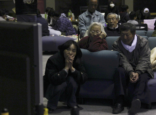 Evacuees watch news on a troubled nuclear power plant on television at a makeshift shelter in Fukushima, northern Japan, Tuesday, March 15, 2011, four days after a powerful earthquake-triggered tsunami hit the country's east coast. (AP Photo/The Yomiuri Shimbun, Koichi Nakamura)