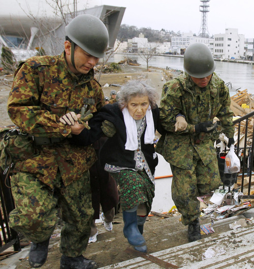 Fujiko Chiba, who was stranded in an isolated evacuation center for five days, is rescued by Japan Ground Self-Defense Force members in Ishinomaki, Miyagi Prefecture northern Japan, Tuesday March 15, 2011, after Friday's earthquake and tsunami, (AP Photo/Kyodo News)