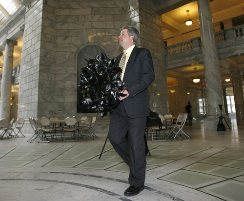 Steve Griffin  |  The Salt Lake Tribune   David Cuillier, SPJ Freedom of Information Committee chairman, carries a black wreath through the rotunda at the state Capitol on Wednesday, March 16, 2011, after announcing the Society of Professional Journalists had given Utah Governor Gary Herbert and the Utah Legislature the national