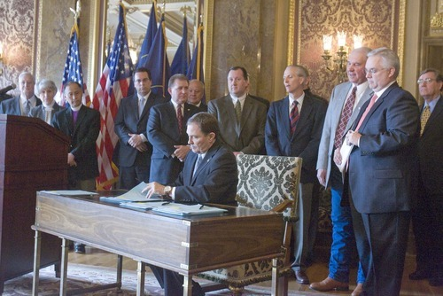 PAUL FRAUGHTON  |  Tribune File Photo   Utah Gov. Gary Herbert on March 15 signed into law immigration  bills passed in this year's legislative session, including a controversial guest-worker plan. The signing ceremony included leading lawmakers, LDS Presiding Bishop H. David Burton, far left, Sutherland Institute President Paul Mero, fourth from left, and Salt Lake Chamber of Commer President Lane Beattie, sixth from left.