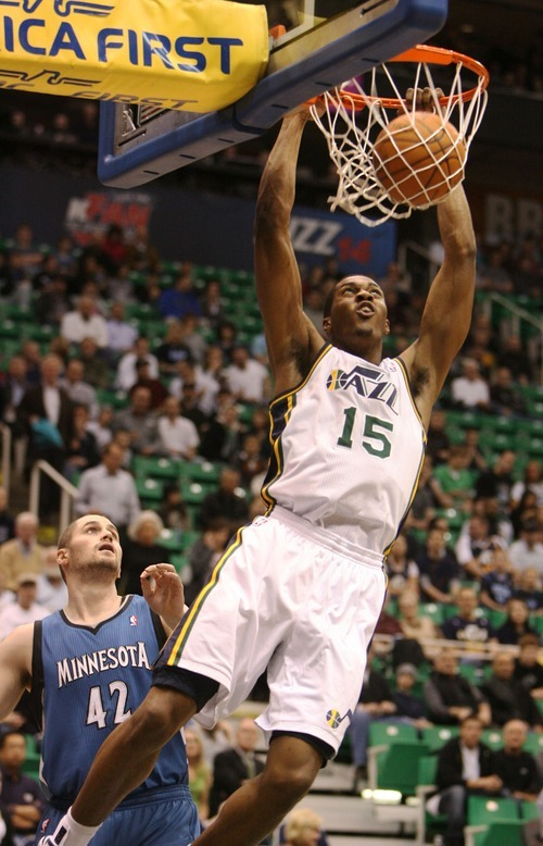 Steve Griffin  |  The Salt Lake Tribune   Utah Jazz forward Derrick Favors slams the ball after driving around Minnesota's Kevin Love during a game against the Timberwolves at EnergySolutions Arena  in Salt Lake City on Wednesday, March 16, 2011.