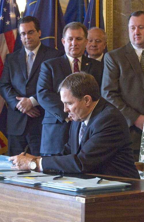 PAUL FRAUGHTON  |  Tribune File Photo With religious, community, business and government leaders behind him, Utah Gov. Gary Herbert on March 15 signed legislation that grew out of the Utah Compact statement of principles. The bills included a controversial guest-worker program (HB116) and an enforcement bill (HB497).