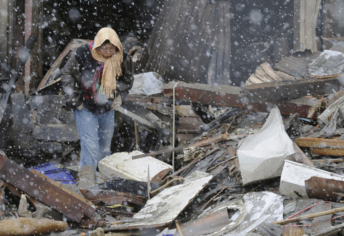 Kyodo News     The Associated Press Braving falling snow, a woman looks around in the rubble Wednesday in Kesennuma, Miyagi Prefecture, five days after an earthquake-triggered tsunami devastated northeastern coastal towns in Japan.